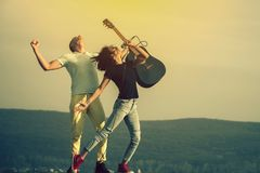 Young couple of musicians performing on natural stage. Pretty woman, singer or girl singing to mic and handsome men playing acoustic guitar on sunny, summer royalty free stock photography