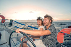 Young couple navigating on a yacht Stock Photos