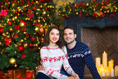 Young couple near fireplace celebrating Christmas Stock Images