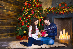 Young couple near fireplace celebrating Christmas Royalty Free Stock Images