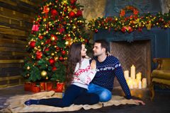 Young couple near fireplace celebrating Christmas Royalty Free Stock Photography