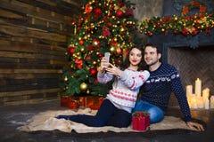 Young couple near fireplace celebrating Christmas Stock Image