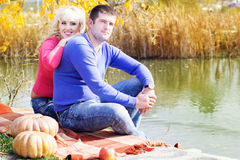 Young couple near lake with pumpkin, autumn time Royalty Free Stock Image