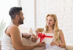 Young Couple Near Window Happy Smile Hispanic Man Woman Hold Present Envelope With Ribbon Lovers In Bedroom Stock Images
