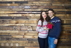 Young couple near wooden wall celebrating Christmas Stock Photography