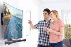 Young Couple With New Curved Screen Television At Home Stock Image