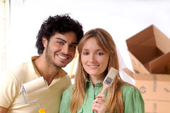 Young couple and new home. Couple in new home with brush for to paint wall Royalty Free Stock Image