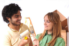 Young couple and new home. Young couple in new home with brush for to paint wall Stock Images