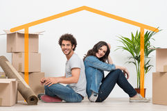 Young Couple At New Home. Smiling Young Couple Sitting Back To Back After Moving House Royalty Free Stock Photo