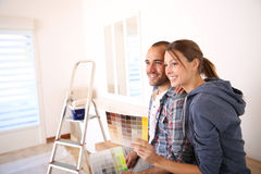 Young couple in new house decorating walls Stock Image