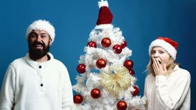 Young couple in New Year`s hats show emotions of surprise on blue background. New Year`s Concept. Bearded man and. Beautiful woman near Christmas tree on blue stock footage