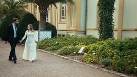 Young couple of newlyweds in love are walking in park between beautiful plants. stock video footage