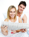 Young couple with a newspaper in bed Royalty Free Stock Photo