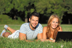 Young couple with a notebook in the park Royalty Free Stock Photography