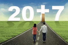 Young couple with number 2017 and a cross. Image of young couple standing on the road while looking number 2017 with a cross symbol Royalty Free Stock Images