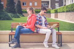 Young couple obsessed with modern technologies ignoring each other stock photo