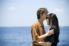 Young couple by ocean. A young man kssing the forehead of a young woman by the water royalty free stock photography