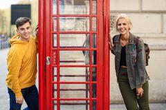 Young Couple Of Friends Near A Classic British Red Phone Booth Royalty Free Stock Images