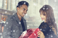 Young couple offering a Christmas present Royalty Free Stock Images