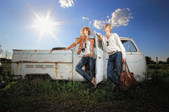 A young couple on a old car in a field Royalty Free Stock Images