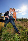 A young couple on a old car in a field Royalty Free Stock Photo