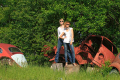 A young couple on a old car in a field Royalty Free Stock Photos