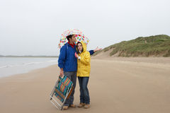 Young Couple On Beach With Umbrella Stock Images