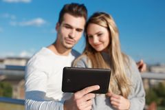 Young couple online shopping by tablet outdoor DOF Stock Photography