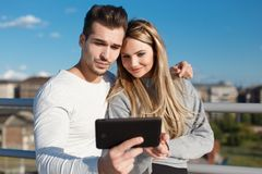 Young couple online shopping by tablet outdoor Royalty Free Stock Photos