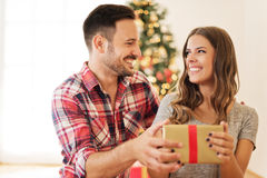 Young couple opening a Christmas present on a Christmas morning Royalty Free Stock Images