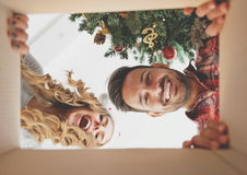 Young couple opening a christmas present. View from inside of the box Royalty Free Stock Image