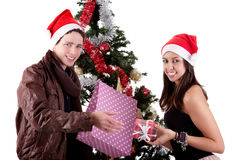 Young couple, opening gifts beside Christmas tree Royalty Free Stock Photos