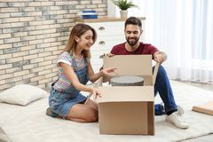 Young couple opening parcel on floor stock photo
