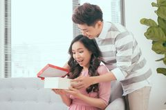 Young couple opening parcel gift box on the couch stock image