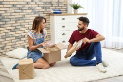 Young couple opening parcels on floor stock images