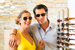 Young couple at optician with glasses Royalty Free Stock Photography
