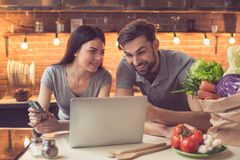 Young couple ordering food online. Order food online. Young beautiful couple in kitchen ordering food online from restaurant. Family of two using laptop. Young Stock Photos
