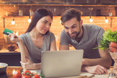 Young couple ordering food online. Order food online. Young beautiful couple in kitchen ordering food online from restaurant. Family of two using laptop. Young Stock Photography