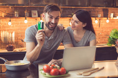 Young couple ordering food online. Order food online. Couple in kitchen ordering food online from restaurant. They using laptop. Man looking at camera and Stock Images