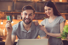 Young couple ordering food online. Order food online. Couple in kitchen ordering food online from restaurant. They using laptop. Man looking at camera and Stock Photos