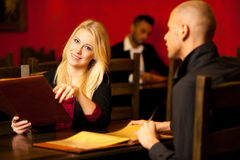 Young couple ordeting food in restaurant reading menu Stock Photography