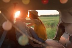 Young couple sitting in their car trunk and watching the sunset stock photos