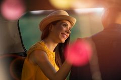 Young couple sitting in their car trunk and watching the sunset royalty free stock images