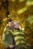 Young couple outdoor at autumn. Young love couple hugging outdoor in park at autumn, smiling Stock Photo