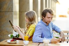Young couple in the outdoor cafe. Young couple using smart phone and tablet pc in the outdoor cafe stock photo