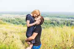 Young couple outdoor portrait. Beautiful pretty girl kissing handsome boy. Sensual photo stock photography