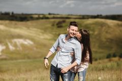 Young couple outdoor portrait. Beautiful pretty girl kissing handsome boy. Sensual photo. royalty free stock photography