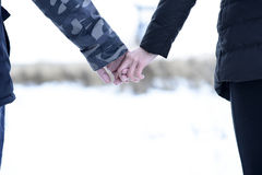 Young couple outdoors, holding hands in a winter park. Touching of young, families. Young couple outdoors, holding hands in a winter park. Touching hands of a Stock Images