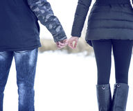 Young couple outdoors, holding hands in a winter park. Touching of young, families. Young couple outdoors, holding hands in a winter park. Touching hands of a Stock Photo