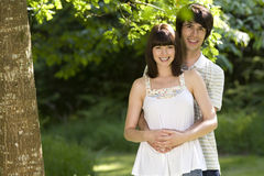 Young couple outdoors, man embracing woman, smiling, portrait Royalty Free Stock Photography